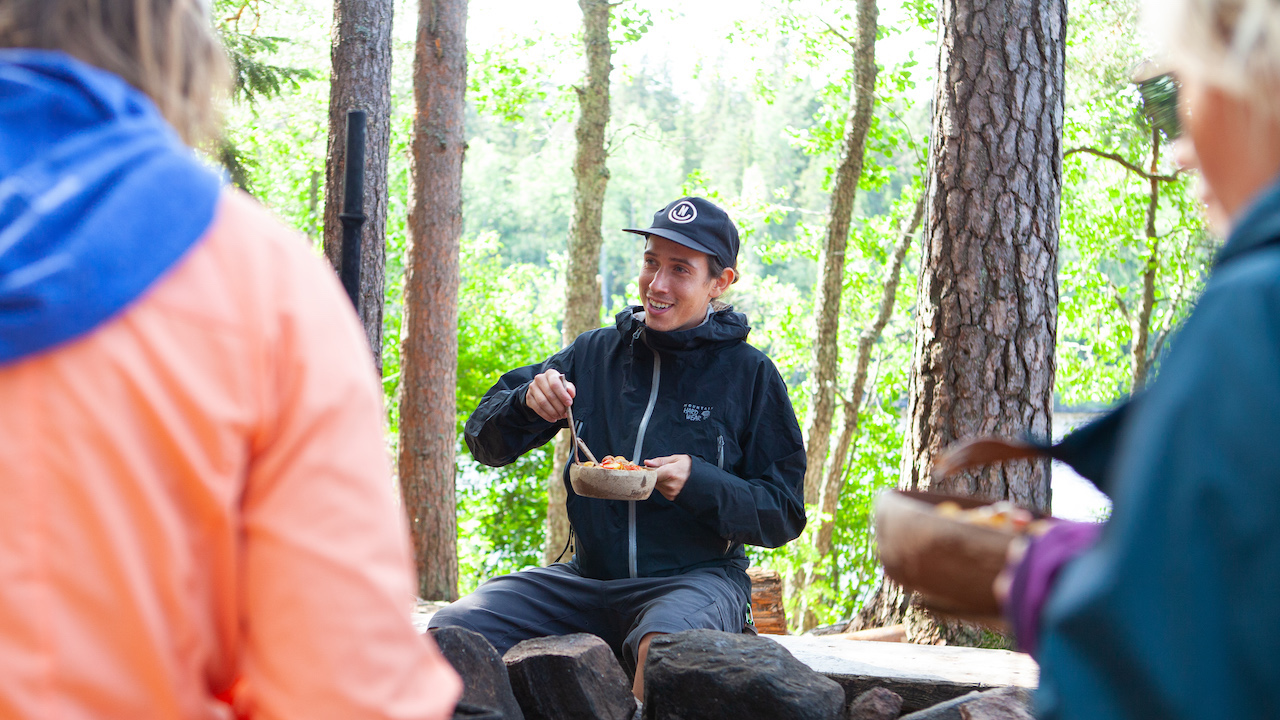 people eating lunch around a camp fire in a nature