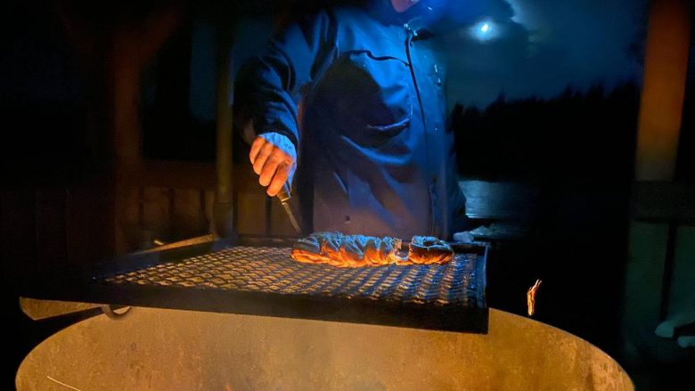 guide cooking over a campfire during nighttime