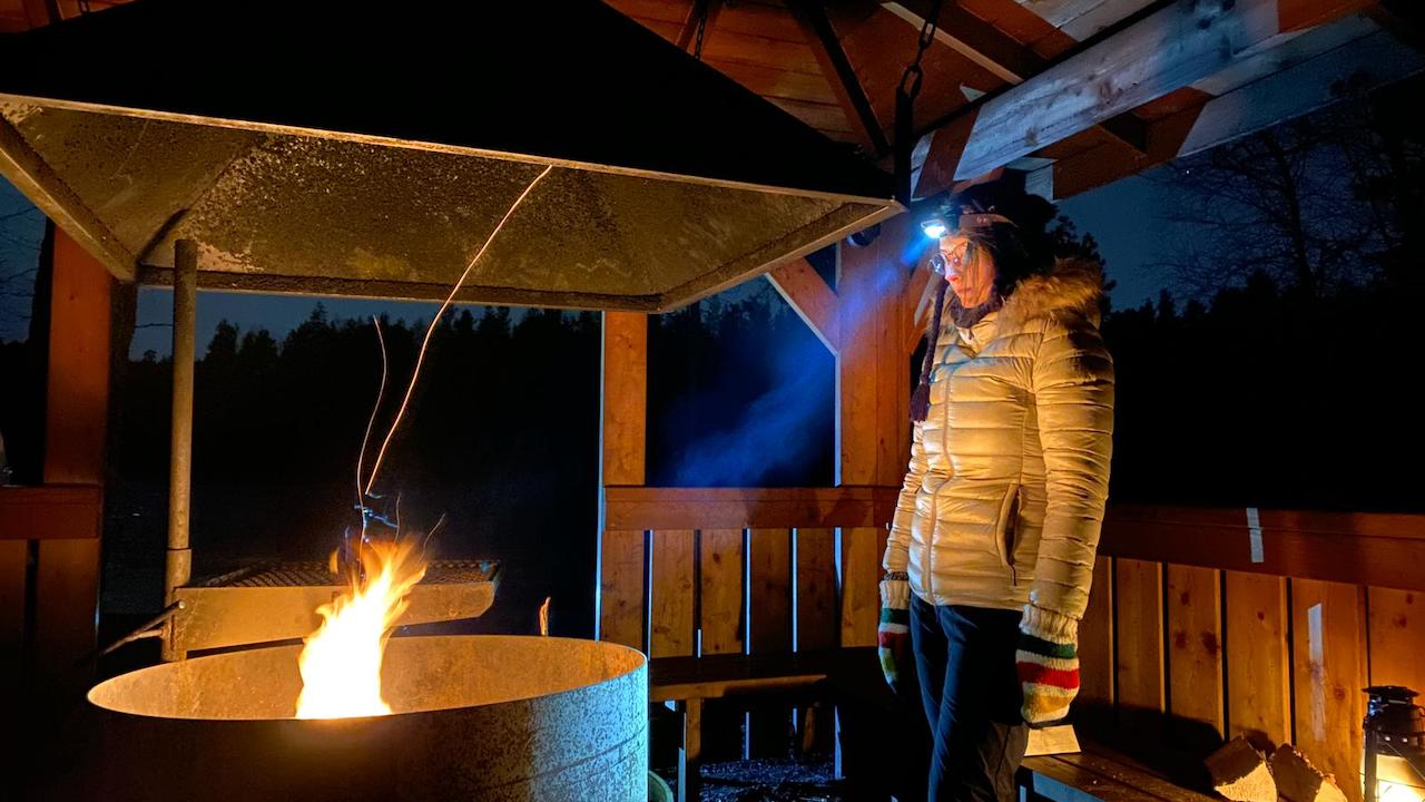 guest looking at campfire during nighttime inside a hut