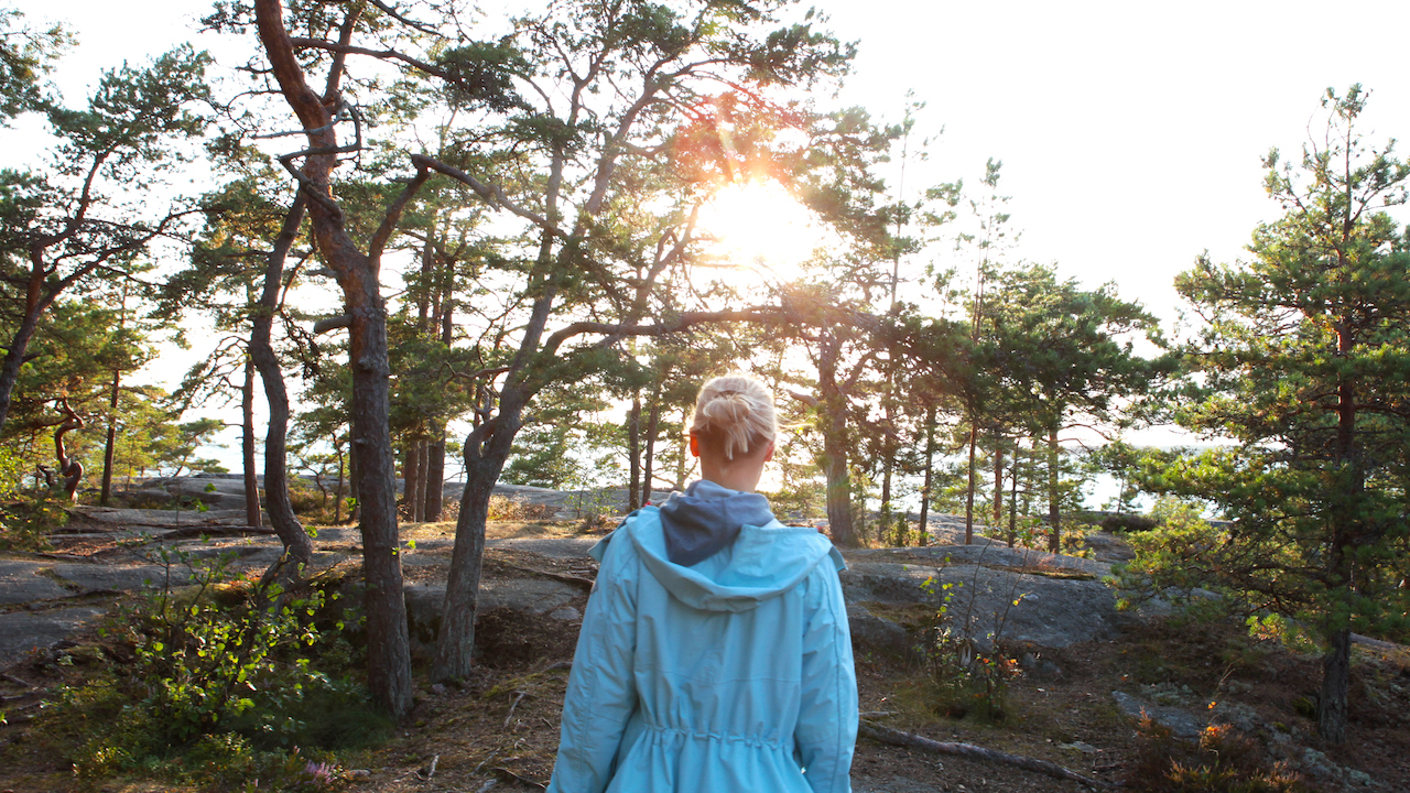 woman walking in archipelago near by helsinki during midnight sun