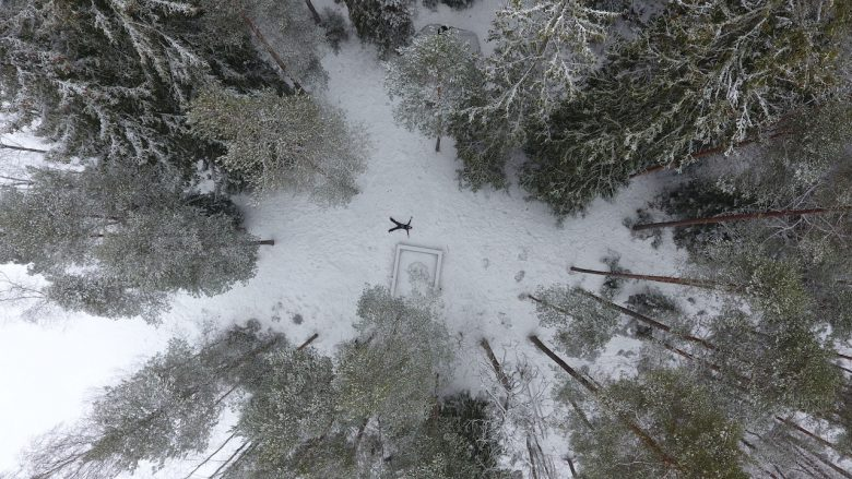 drone picture of woman laying in a national park winter