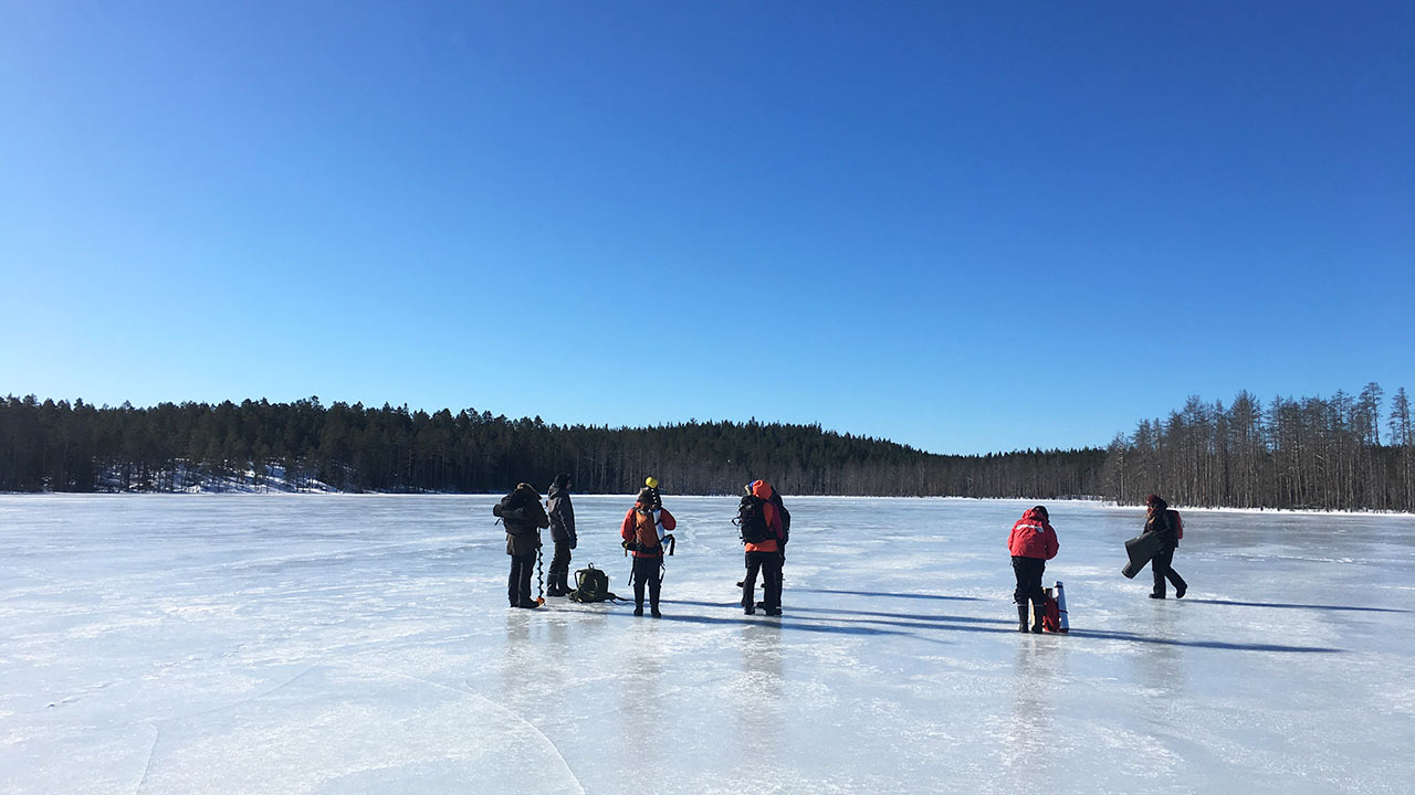 people standing on a frozen lake preparing to ice fish