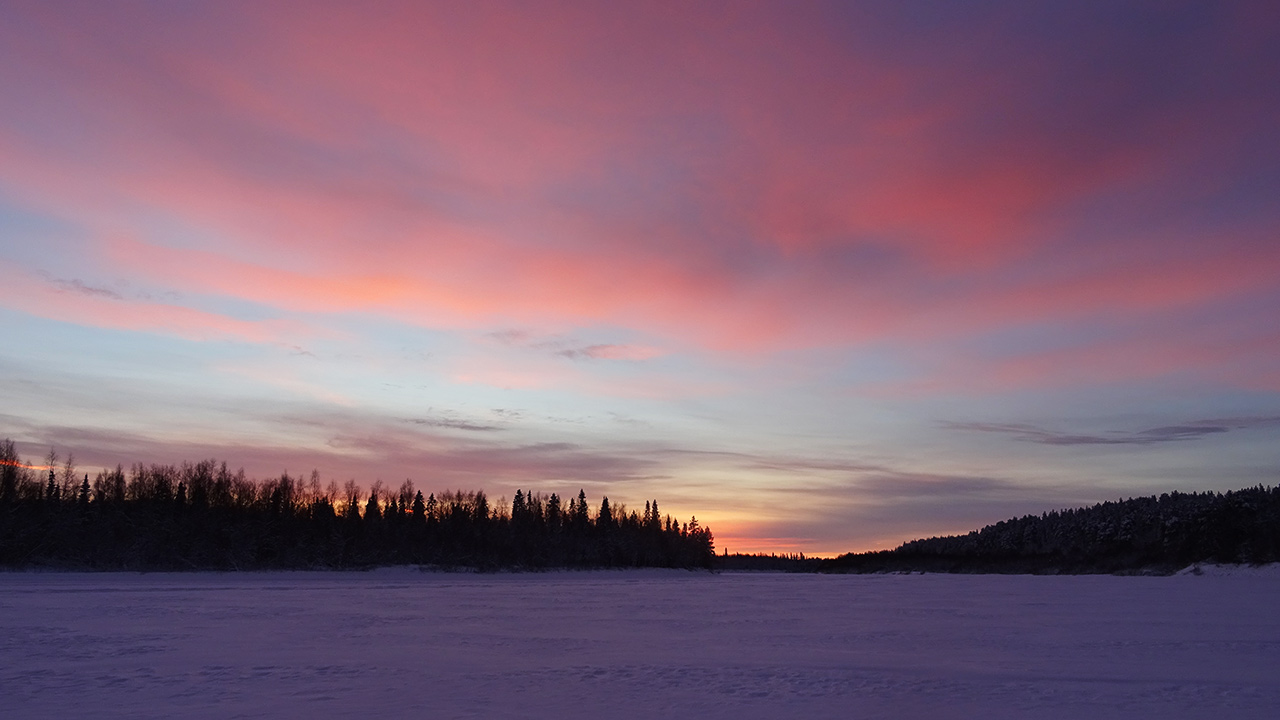 lapland sunset overlooking frozen ivalo river