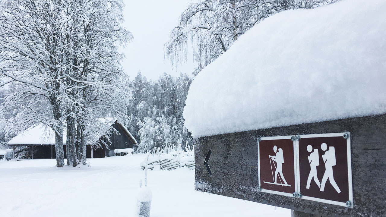 wooden sign in a finnish national park covered in snow