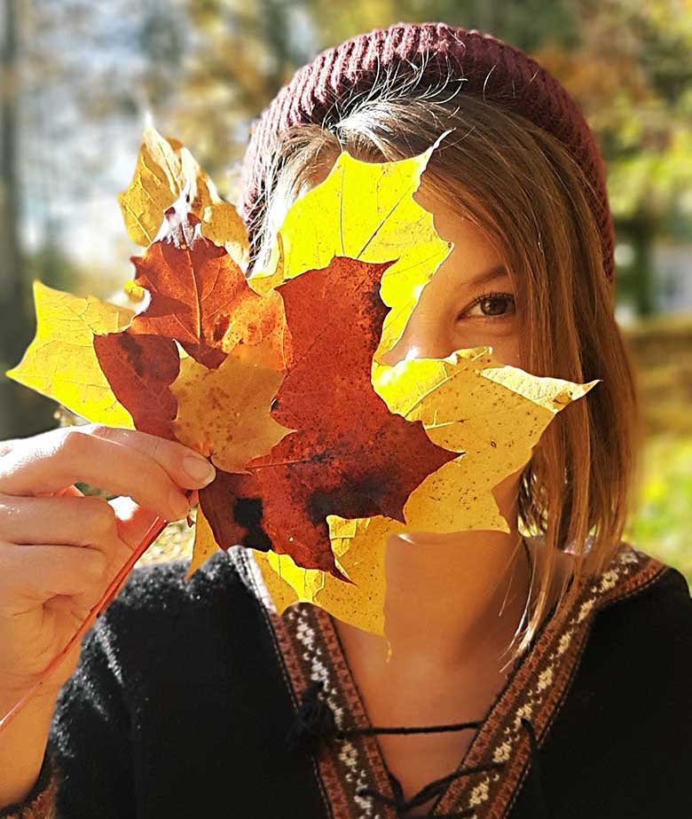 girl playing with autumn colours in nature