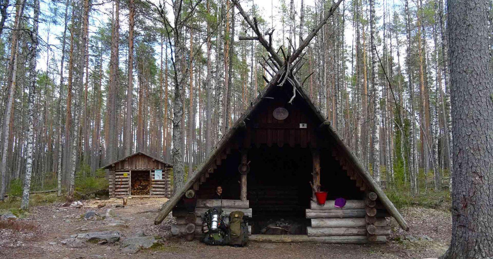 a qoman sitting inside of a wilderness hut in finnish national park