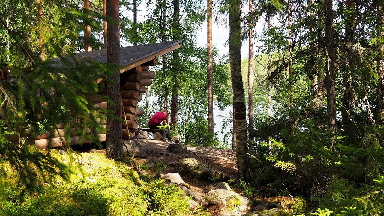 a man sitting on a leaning-on-hut by a lake in isojarvi national park finland